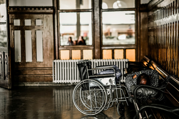 Disabling Condition - Man lying on a bench beside a wheelchair