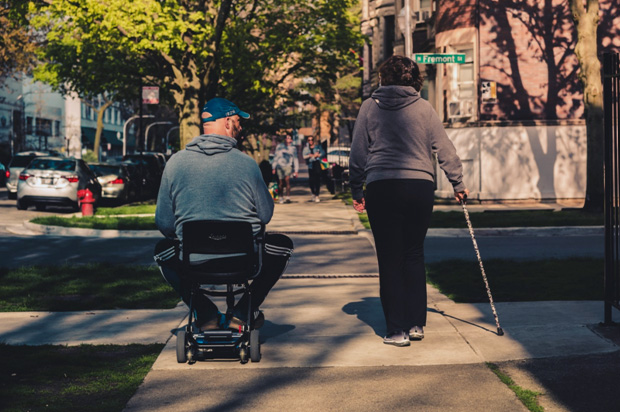 Man in a wheelchair beside a woman with a cane